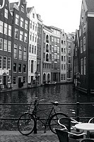 Netherlands, Amsterdam, bicycle parked by canal B&W