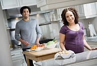 Pregnant African couple preparing food
