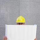 Businessman in hardhat looking at blueprints