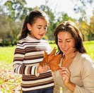 Hispanic mother and daughter looking at autumn leaf