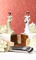 Two female figurines on separate pieces of wedding cake, close-up