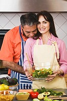 Middle-aged Hispanic couple holding salad