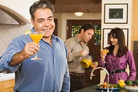 Middle-aged Hispanic man toasting with cocktail