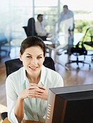 Businesswoman sitting at computer in office smiling