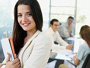 Woman in office with documents smiling
