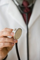 Male doctor holding stethoscope, close-up of hand