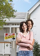 Man and woman embracing in front of house with sold sign