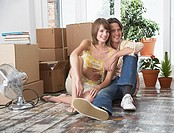 Man and woman sitting on hardwood floor with cardboard boxes and potted plants with fan