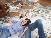Man and woman lying down on bubble wrap in home with cardboard boxes