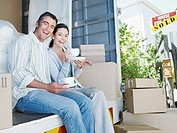 Man and woman with cups sitting in moving van outdoors smiling with sold sign on house