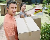 Man and woman carrying cardboard boxes with sold sign in yard