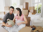 Man and woman in house with boxes unpacking vase