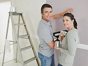 Man and woman in room with paint and ladder