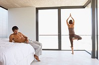 Woman doing yoga with man sitting on bed