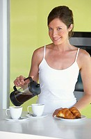 Woman in kitchen with coffee and croissants smiling