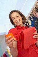 Woman looking at sales tag on purse (thumbnail)