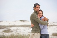 Man and woman on beach embracing (thumbnail)