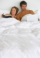 Woman in bed reading and man with laptop
