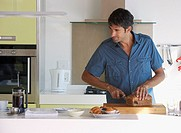 Man in kitchen slicing bread with coffee and baked goods
