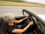 Senior Hispanic woman driving convertible car