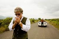 Senior man smoking while wife stands next to car