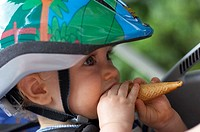 baby with helmet and ice-cream cone in child seat