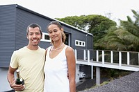 Multi-ethnic couple holding champagne in front of house