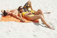 Woman in bikini with MP3 player lying down on man