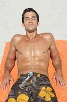 Man lying down on beach towel in sand