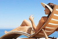 Woman in straw hat sunbathing on wooden chair with beverage