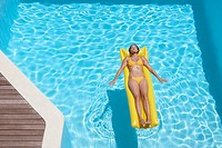 Woman in bikini on flotation device in pool