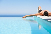 Man on infinity pool deck in swimsuit