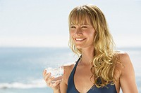Woman smiling outdoors with beverage