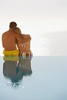 Rear view of man and woman in swimsuits in infinity pool embracing