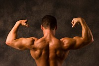 Muscular man flexing back, arm, and shoulder muscles