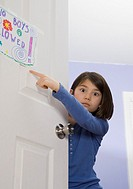 Asian girl pointing at sign on bedroom door