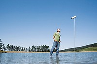 Man standing on water with surveillance camera