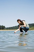 Woman standing on water dipping hand in