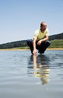 Man crouching on water