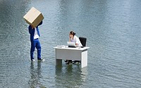 Man delivering cardboard box to woman at desk on water