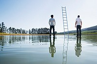 Two men standing on water with ladders
