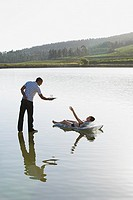 Woman lying on flotation device and man standing on water with beverage