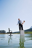 Businesswoman and man standing on desk on water