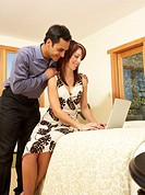 Man looking over shoulder of woman using laptop on bed