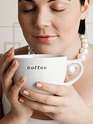 Young plus-size woman holding coffee cup, eyes closed, close-up