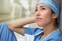 Hispanic female doctor sitting against wall looking up