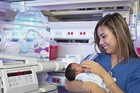 Female nurse feeding newborn African baby next to incubator