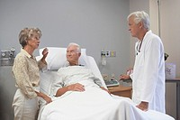 Senior male patient and wife talking to doctor in hospital room
