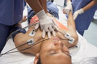 Doctor performing CPR on Asian patient in the emergency room