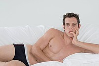 Semi-nude man laying on bed